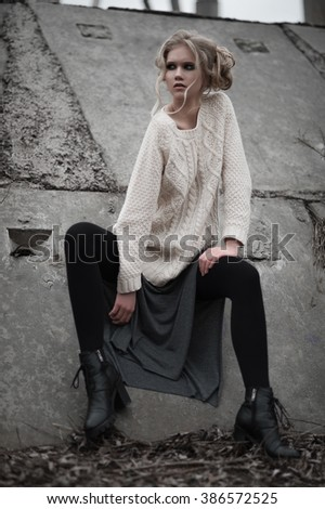 Close up of beautiful young  blonde woman with blue eyes in white pullover, sitting. Winter, spring, outdoor portrait. Professional beauty make-up: dark smoky eyes and pale lips and hair style. - stock photo