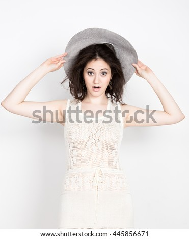 close-up of beautiful young brunette woman holding a broad-brimmed hat, she expression of different emotions
