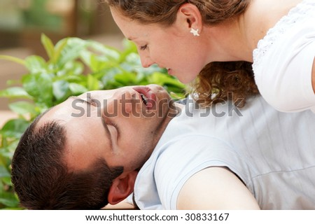 close up  of beautiful young couple about to kiss, the man is laying on his back with his lips open, the woman appears to be smiling - stock photo