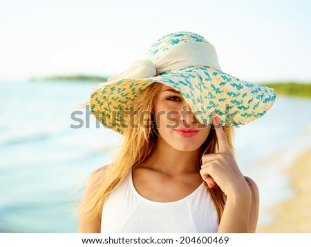 Close-up Of Beautiful Young Woman At Beach Wearing Hat - stock photo