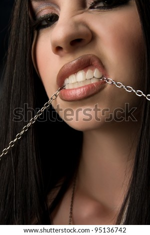 Close-up of beautiful young woman biting a metal chain - stock photo