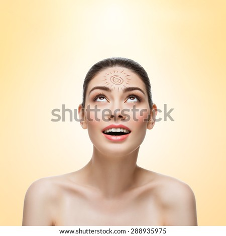 Close-up of beautiful young woman looking up on sun drawing on her forehead. Isolated over beige background. Copy space. Square composition. - stock photo