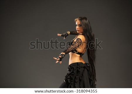 Close up of beautiful, young woman performing tribal dance - stock photo