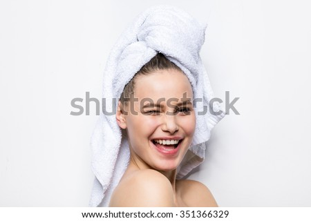 close-up of beautiful young woman with bath towel on head covering her breasts, on white - stock photo