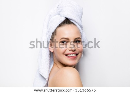 close-up of beautiful young woman with bath towel on head covering her breasts, on white