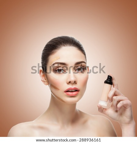 Close-up of beautiful young woman with four shades of liquid foundation on face and bottle in hand. Isolated over brown background. Copy space. Square composition. - stock photo
