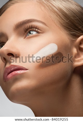 Close-up of beautiful young woman with stokes of foundation on her face - stock photo