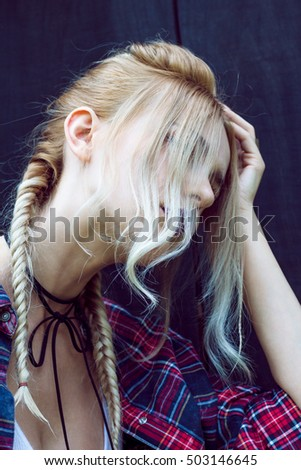 Close up of beautiful young woman with strong dark makeup and purple lips. Professional modern stylish fashionable hairstyle. Created from small and large braids and loose hair.