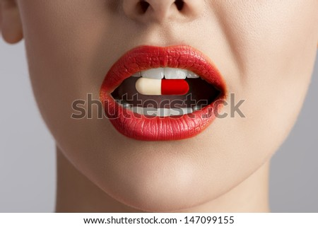 close-up of beauty female mouth with coloured pill between teeth  - stock photo