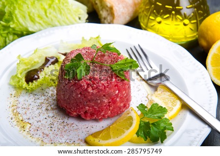 Close up of beef tartar with fresh salad and lemon slice - stock photo