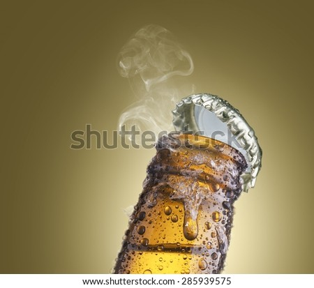 close-up of beer bottleneck with droplets, ice, smoke, and cap - stock photo