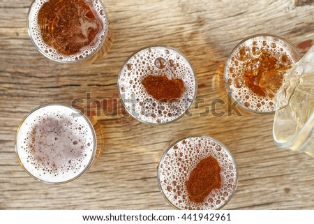 Close-up of beer by the glass, top view. Beer is poured from a jug into a glass. Concept: party, holiday, pub. - stock photo