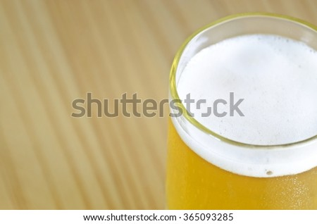 Close up of beer glass with froth - stock photo