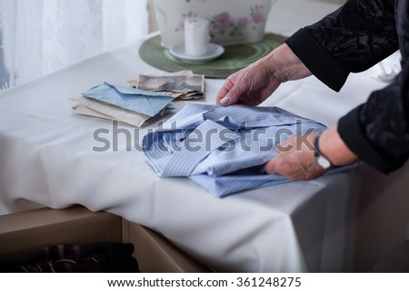 Close up of bereaved female tidying things after dead husband - stock photo