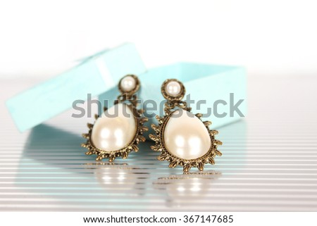 Close-up of big earrings with pearls in a gift box - stock photo