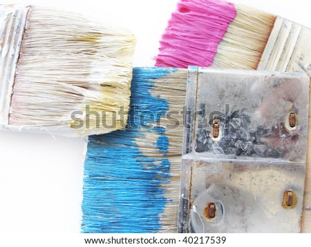 Close up of big old used paintbrushes with cyan and magenta color on white background - stock photo