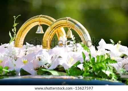 Close-up of big wedding golden rings with bells by white flowers on car roof - stock photo