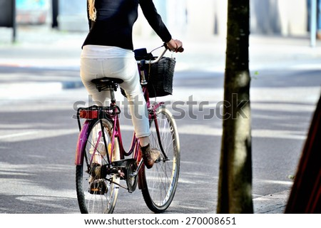 Close up of bike and bicyclist in summer city - stock photo