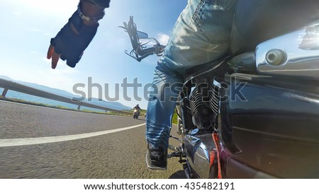 close up of biker greeting on the road - stock photo