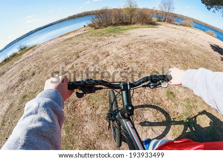 Close-up of biker hand holding the steering wheel. Photographed on a fisheye lens. - stock photo