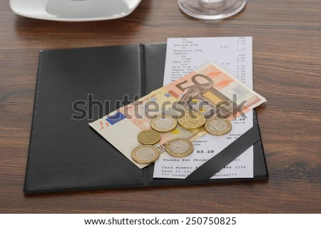 Close-up Of Bill With Euro Note On Wooden Table - stock photo