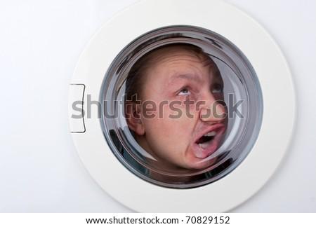 Close-up of bizarre man inside washing machine - stock photo