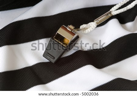 close up of Black and white referee or game official shirt with whistle