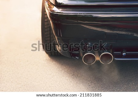 Close-up of black car dual exhaust pipe with smoke - stock photo