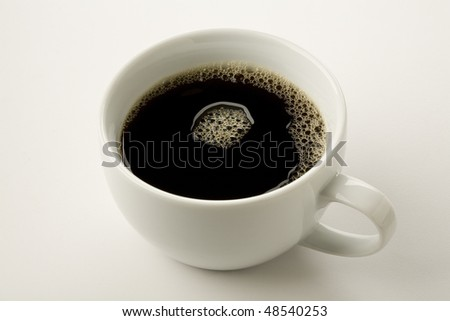 close up of black coffee in white cup with froth - stock photo