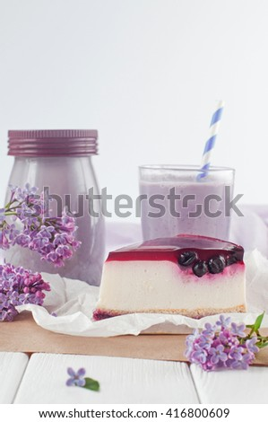 Close up of black currant cheesecake slice near bilberry milkshake and lilac flowers on the white wooden background. Selective focus and small depth of field. - stock photo