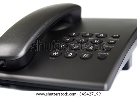 Close-up of black desktop phone. Buttons and part of the handset. Isolated on white background.