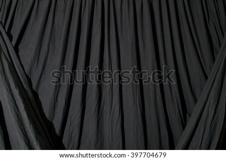 Close up of black draped theatrical curtain or backdrop.