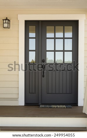 Close Up of Black Front Door on House with Yellow Exterior Siding - stock photo