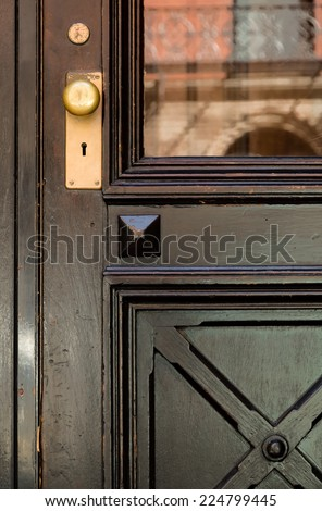 Close-up of Black Front Door with Crosshatch Detail and Gold Doorknob - stock photo