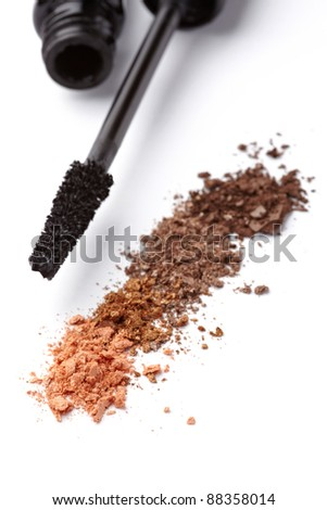 close up of black mascara and face powder on white background - stock photo