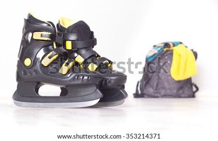 Close up of black plastic ice skates with yellow details and backpack with colorful cap and scarf in background - stock photo