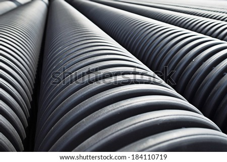 Close up of black plastic pipes with diminishing perspective  - stock photo