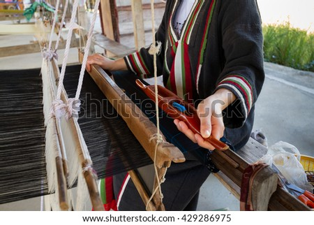 Close up of black silk weaving on loom, selective focus - stock photo