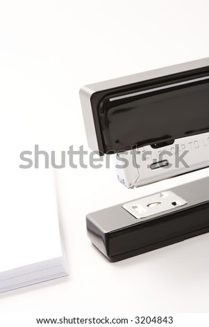 Close up of black stapler on white background with stack of paper.