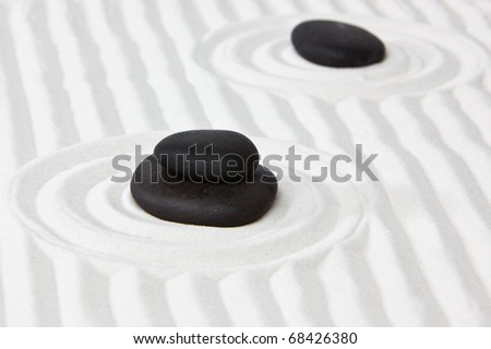 Close-up of black stones on white raked sand in a Japanese ornamental or zen garden. - stock photo