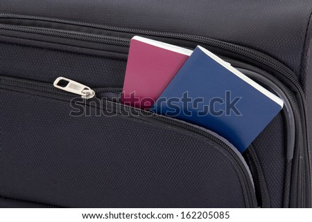 close up of black travel suitcase and two passports - stock photo
