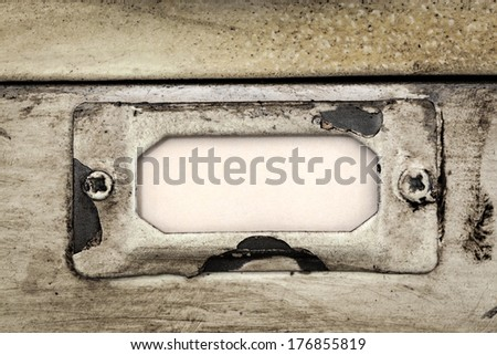 Close up of blank label in metal holder of vintage filing cabinet.  Great grunge textures. - stock photo