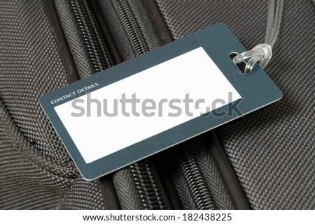 Close up of blank luggage tag on suitcase - stock photo