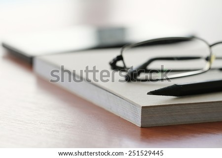 close up of Blank notepad with pencil and glasses on office wooden table