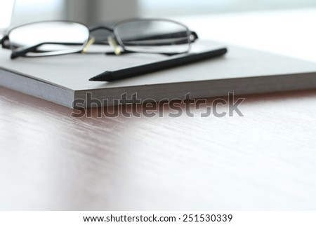 close up of Blank notepad with pencil and glasses on office wooden table - stock photo
