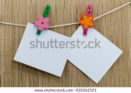 close up of blank paper reminders and clothespins attached to a rope on bamboo mats - stock photo