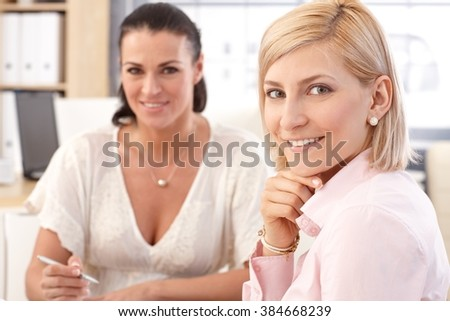 Close up of blonde casual, smiling businesswoman at office meeting, looking at camera. - stock photo