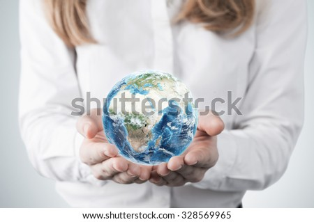 Close-up of blonde's hands who holds the globe with Africa, Europe and Asia hemisphere. A woman dressed in formal clothes. A light grey background. Elements of this image furnished by NASA. - stock photo