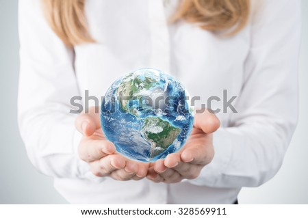 Close-up of blonde's hands who holds the globe with western hemisphere. A woman dressed in formal clothes. A light grey background. Elements of this image furnished by NASA.