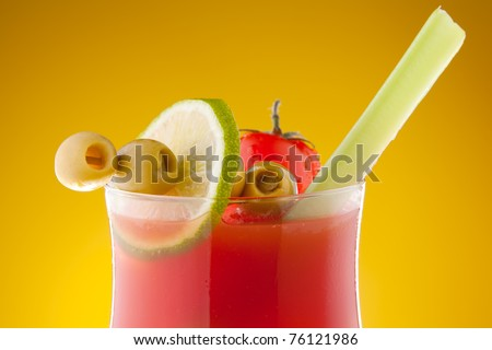 Close-up of bloody Mary cocktail in glass with olives, lime and celeriac - stock photo